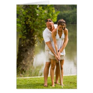 Man helping woman golf cards