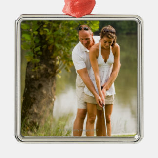 Man helping woman golf christmas ornament