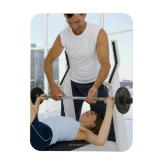 Man helping woman with weightlifting rectangle magnets