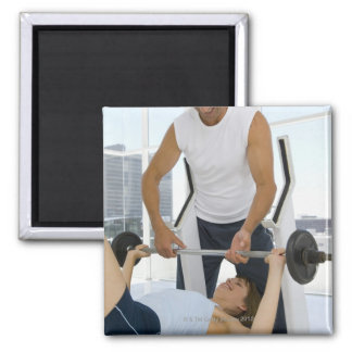 Man helping woman with weightlifting square magnet