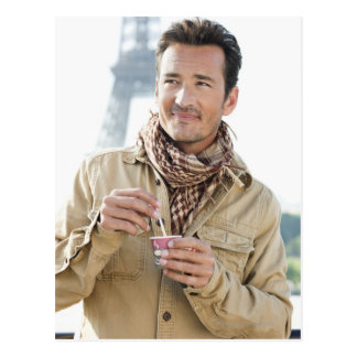 Man holding a disposable cup with the Eiffel Postcard