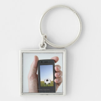 Man holding a mobile phone key chains