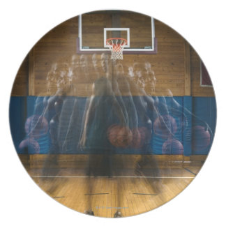 Man holding basketball standing on court, plate