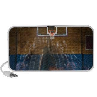 Man holding basketball standing on court, laptop speaker