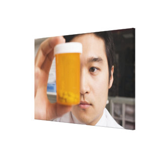 Man holding pill bottle canvas print