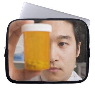 Man holding pill bottle laptop sleeve