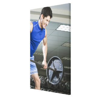 Man in gym, lifting large barbell, clenching canvas print