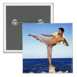 Man in martial arts kicking position, on beach, 15 cm square badge