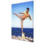 Man in martial arts kicking position, on beach, stretched canvas prints