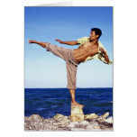 Man in martial arts kicking position, on beach, greeting card
