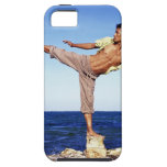 Man in martial arts kicking position, on beach, iPhone 5 cases