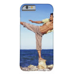 Man in martial arts kicking position, on beach, iPhone 6 case