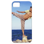 Man in martial arts kicking position, on beach, case for the iPhone 5