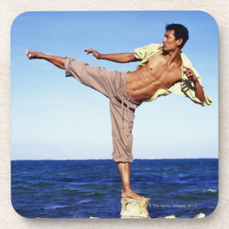 Man in martial arts kicking position, on beach, coaster