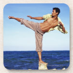 Man in martial arts kicking position, on beach, drink coasters