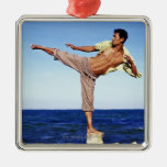 Man in martial arts kicking position, on beach, ornaments