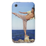 Man in martial arts kicking position, on beach, iPhone 3 Case-Mate cases