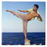Man in martial arts kicking position, on beach, large square tile