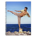 Man in martial arts kicking position, on beach, spiral note book