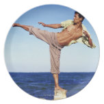Man in martial arts kicking position, on beach, party plate