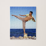 Man in martial arts kicking position, on beach, puzzle