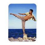 Man in martial arts kicking position, on beach, rectangular photo magnet