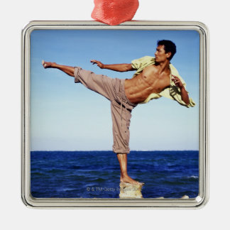 Man in martial arts kicking position, on beach, Silver-Colored square decoration