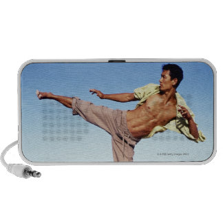 Man in martial arts kicking position, on beach, travelling speaker