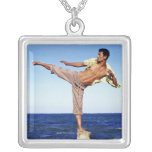 Man in martial arts kicking position, on beach, square pendant necklace