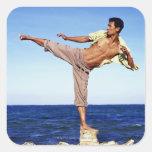 Man in martial arts kicking position, on beach, sticker