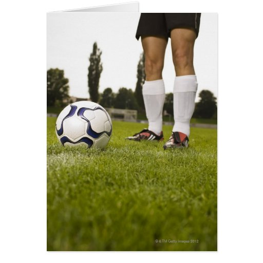 Man in soccer uniform standing with soccer ball greeting card