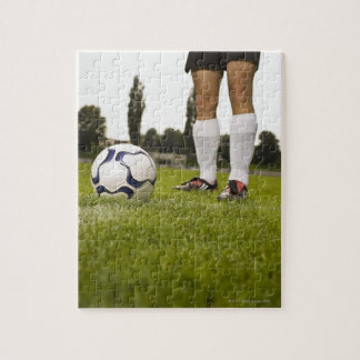 Man in soccer uniform standing with soccer ball jigsaw puzzle