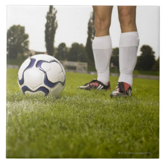 Man in soccer uniform standing with soccer ball large square tile