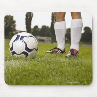 Man in soccer uniform standing with soccer ball mouse mat