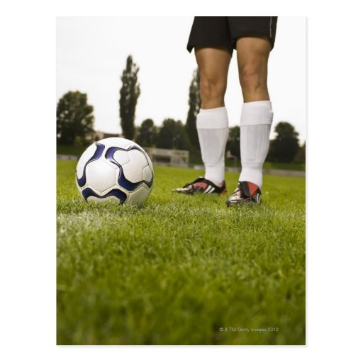 Man in soccer uniform standing with soccer ball post card