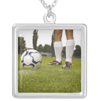 Man in soccer uniform standing with soccer ball silver plated necklace