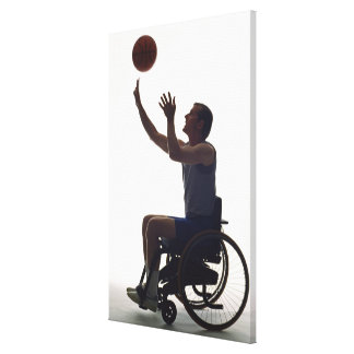 Man in wheelchair playing with basketball canvas prints