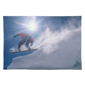 Man jumping off a large cornince on a snowboard placemat