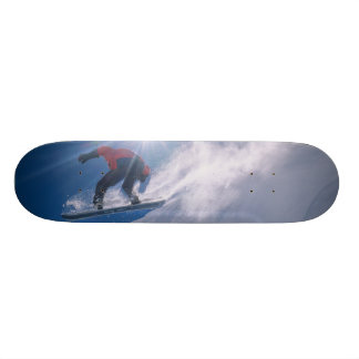 Man jumping off a large cornince on a snowboard skateboards