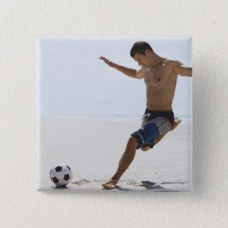 Man kicking soccer ball on beach 15 cm square badge