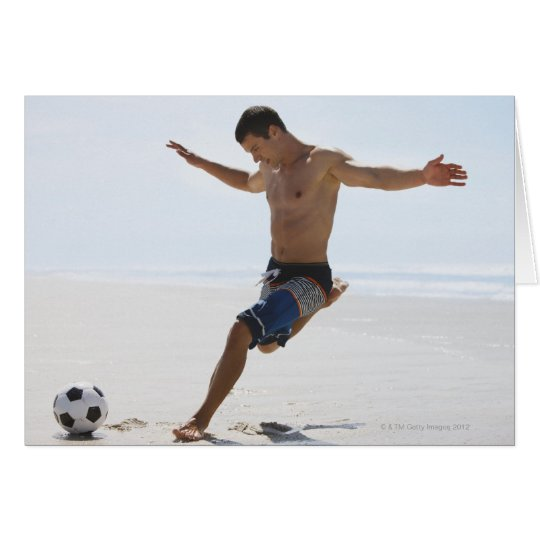 Man kicking soccer ball on beach card