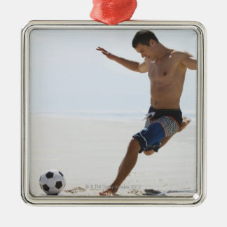 Man kicking soccer ball on beach Silver-Colored square decoration