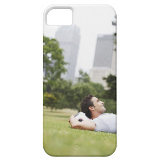 Man laying in urban park with soccer ball case for the iPhone 5