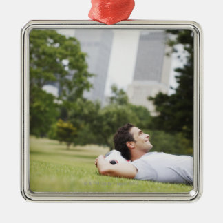 Man laying in urban park with soccer ball christmas ornament