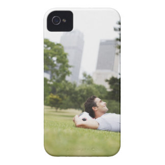 Man laying in urban park with soccer ball iPhone 4 cover