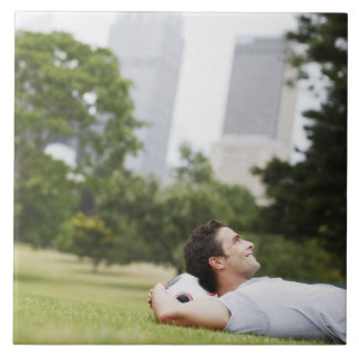 Man laying in urban park with soccer ball tile