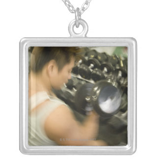 Man lifting dumbbell in gym, high angle view, square pendant necklace