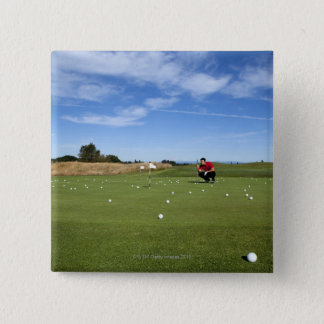 Man lining up a putt while golfing. 15 cm square badge