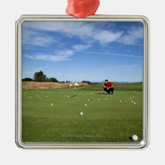 Man lining up a putt while golfing. Silver-Colored square decoration