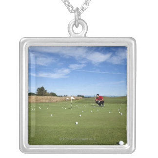 Man lining up a putt while golfing. silver plated necklace